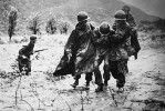Capt. Emil Kapaunk, right, former chaplain with 1st Cavalry Division, helps another soldier carry an exhausted troop off the battlefield early in the Korean War.